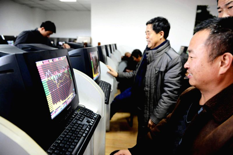 Investors read stock information at a trading hall of a securities firm in Qingdao City, east China's Shandong Province, Dec. 5, 2014. Combined daily turnover of China's Shanghai and ...