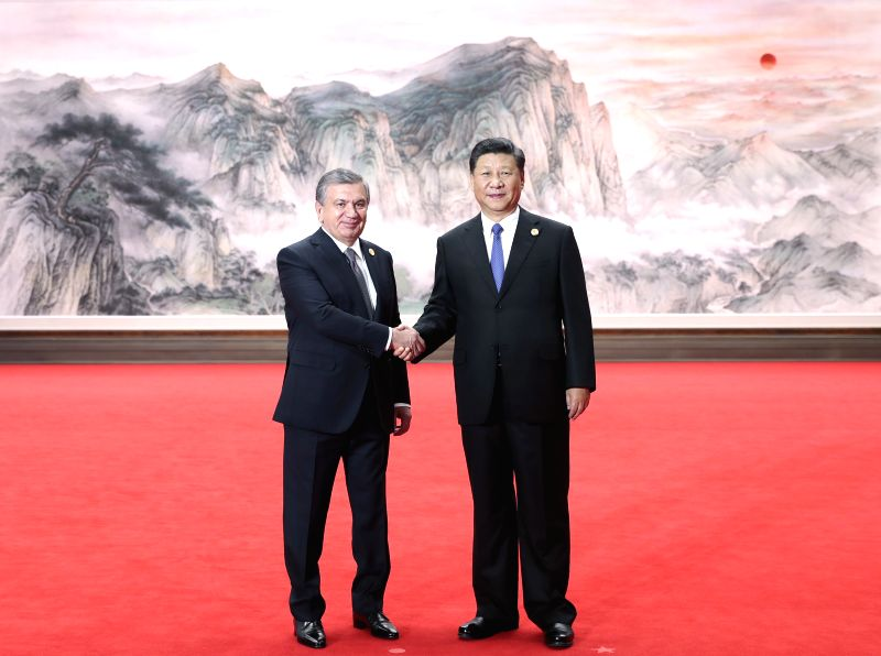 QINGDAO, June 10, 2018 - Chinese President Xi Jinping (R) shakes hands with Uzbek President Shavkat Mirziyoyev ahead of a restricted session of the 18th Shanghai Cooperation Organization (SCO) summit ...
