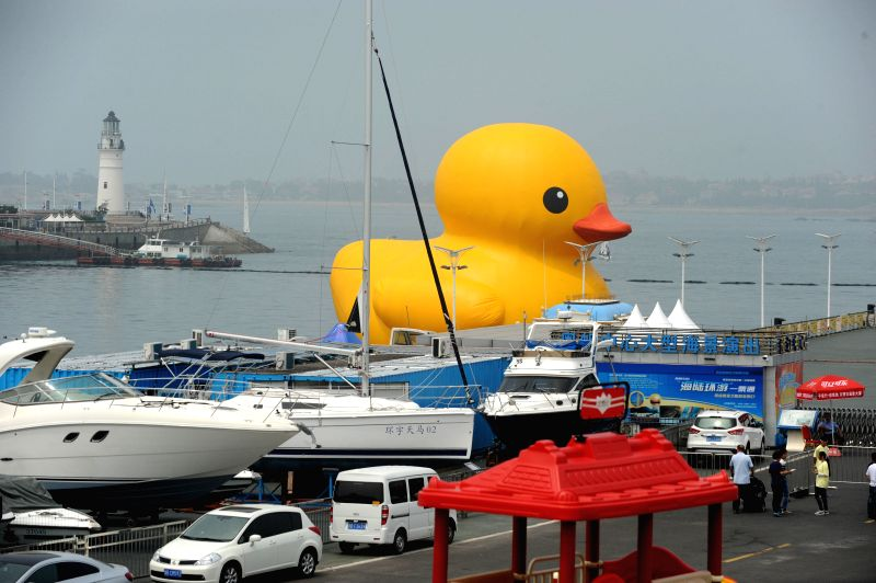 A giant rubber duck, the brainchild of Dutch artist Florentijn Hofman, is seen at Qingdao Olympic Sailing Center in Qingdao, east China's Shandong Province, June ... - Florentijn Hofman