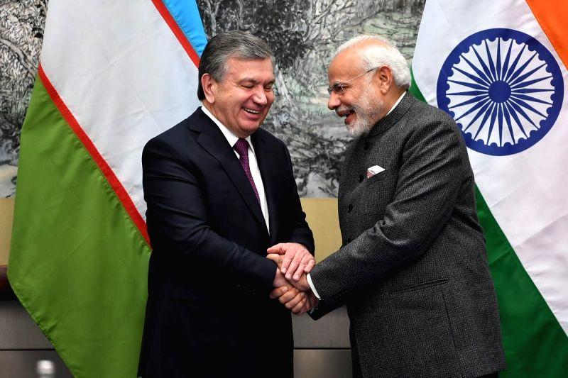 :Qingdao: Prime Minister Narendra Modi meets Uzbekistan President Shavkat Mirziyoyev on the sidelines of the Shanghai Cooperation Organisation (SCO) Summit in Qingdao, China on June 9, 2018. ...