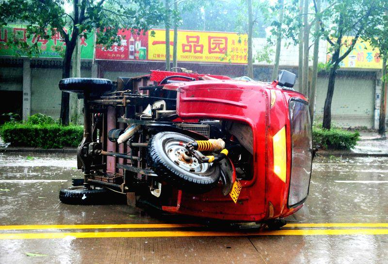 Photo taken on July 19, 2014 shows an overturned vehicle due to the super typhoon Rammasun in Qinzhou City of Guangxi Zhuang Autonomous Region. Typhoon Rammasun, ...