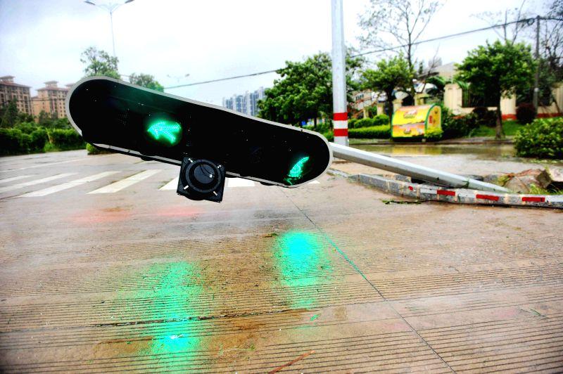 Photo taken on July 19, 2014 shows a traffic light toppled due to the super typhoon Rammasun in Qinzhou City of Guangxi Zhuang Autonomous Region. Typhoon Rammasun, .