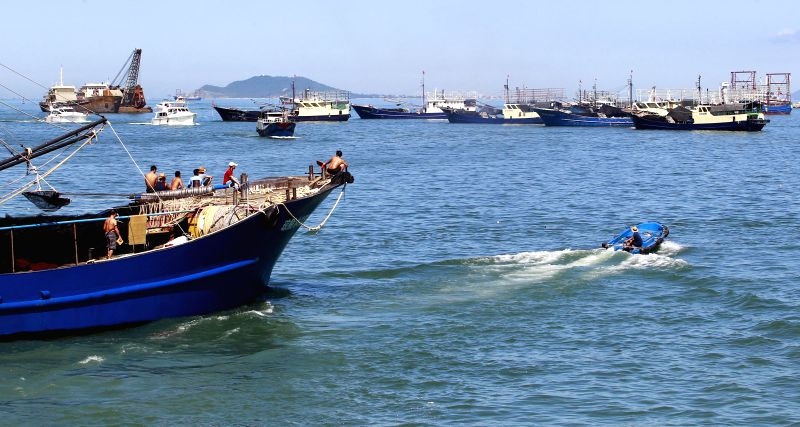 Photo taken on Aug. 1, 2014 shows fishing boats sail out of the port of Sanya, south China's Hainan Province. The annual fishing moratorium in Hainan, which lasts ...