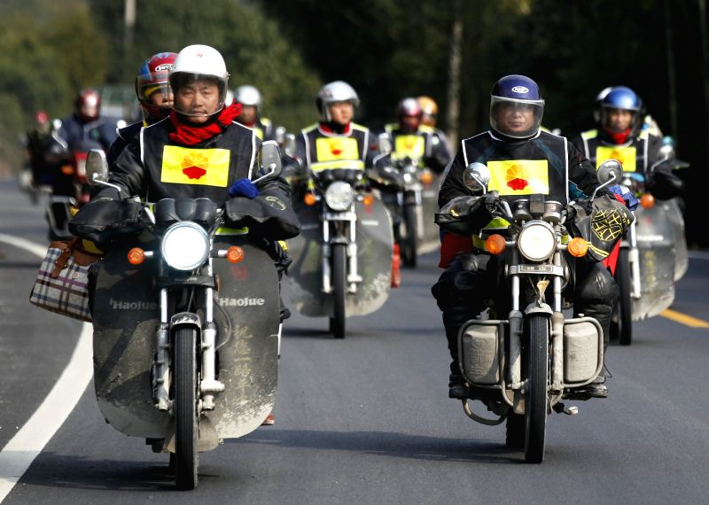 Zhongfu Linsheng (L, front) carries his wife by riding a motorcycle on the way to returning home in Jiubao Township in Ruijin City, east China's Jiangxi Province, .