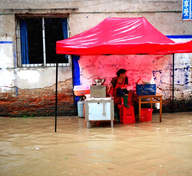 A woman sells breakfast on a flooded road in Quanzhou County of Guilin City, south China's Guangxi Zhuang Autonomous Region, June 18, 2014. A rainstorm hit seven ..