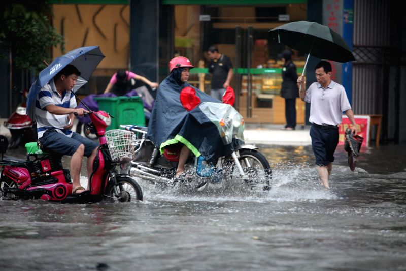 Residents ride motorcycles on a flooded road in Quanzhou County of Guilin City, south China's Guangxi Zhuang Autonomous Region, June 18, 2014. A rainstorm hit ...