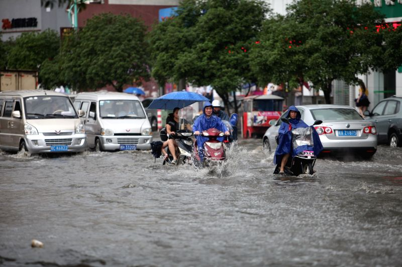 Residents ride motorcycles on a flooded road in Quanzhou County of Guilin, south China's Guangxi Zhuang Autonomous Region, June 18, 2014. A rainstorm hit seven ...