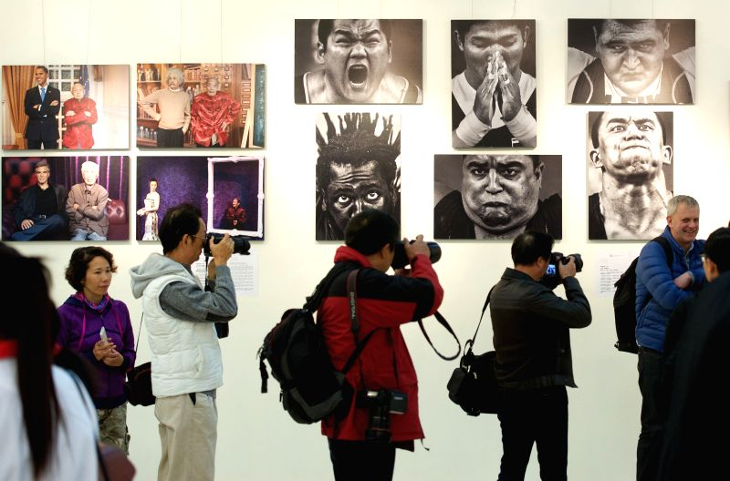 Visitors watch an exhibition of winning photos of the 10th China International Press Photo Contest (CHIPP) in Quanzhou, southeast China's Fujian Province, Dec. 6, 2014. The awarding ...
