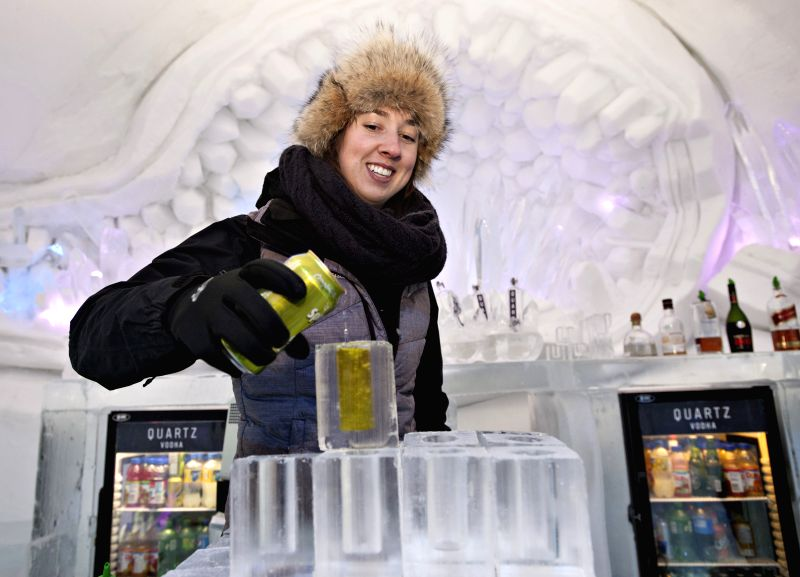 The photo taken on Feb. 6, 2015 shows a woman preparing drinks in an ice hotel which is presented to the public in the north f Quebec City, Canada. The hotel that ..
