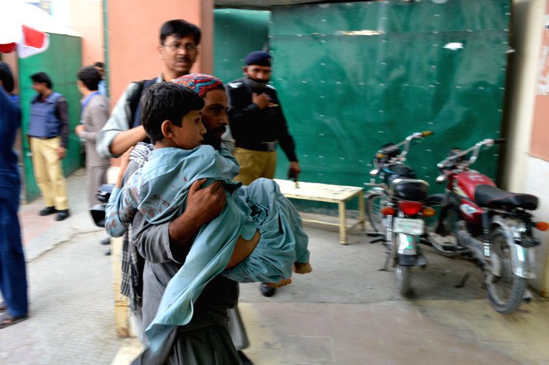 QUETTA,A man carries an injured child at a hospital in southwest Pakistan's Quetta on July 13, 2018. At least 30 people were killed and 60 others injured after a ...