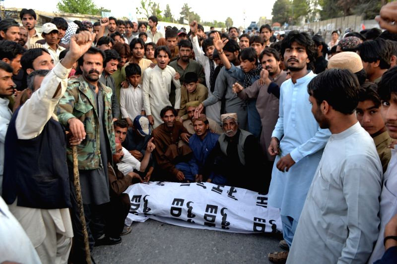Pakistani people shout slogan beside a victim's body in southwest Pakistan's Quetta on April 15, 2014. At least two people were killed and one other was injured as .