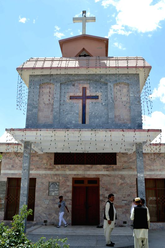 Pakistani Christians stand outside a church after a service at a church in southwest Pakistan's Quetta, April 18, 2014. Christian believers around the world mark ...