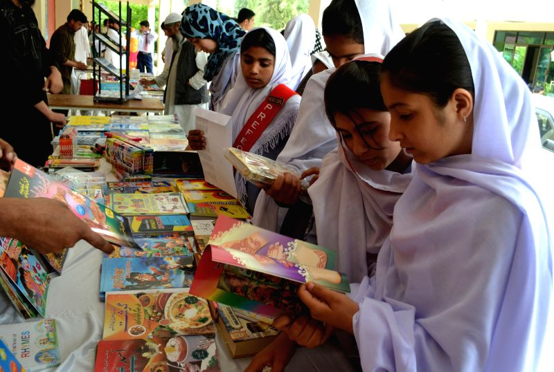 Students read books at a book stall on World Book Day in southwest Pakistan's Quetta on April 23, 2014.