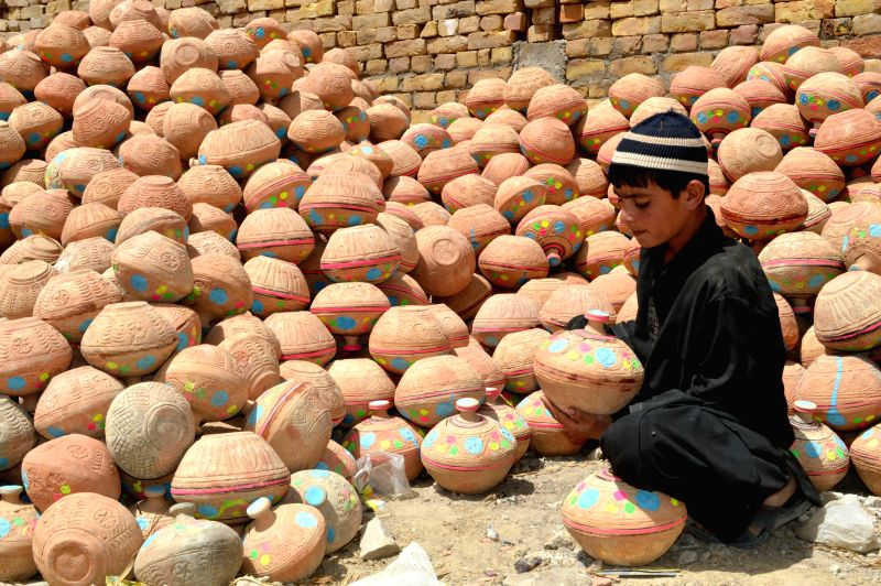 A Pakistani boy arranges pottery at a workshop in southwest Pakistan's Quetta, April 29, 2015. The inflation had touched the decade's lowest level of 2.5 percent in ...