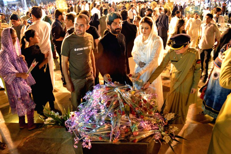 Pakistani Army officers and civilians place flowers during a ceremony to pay tribute to Pakistani paramilitary soldiers who sacrificed their own lives for the ...