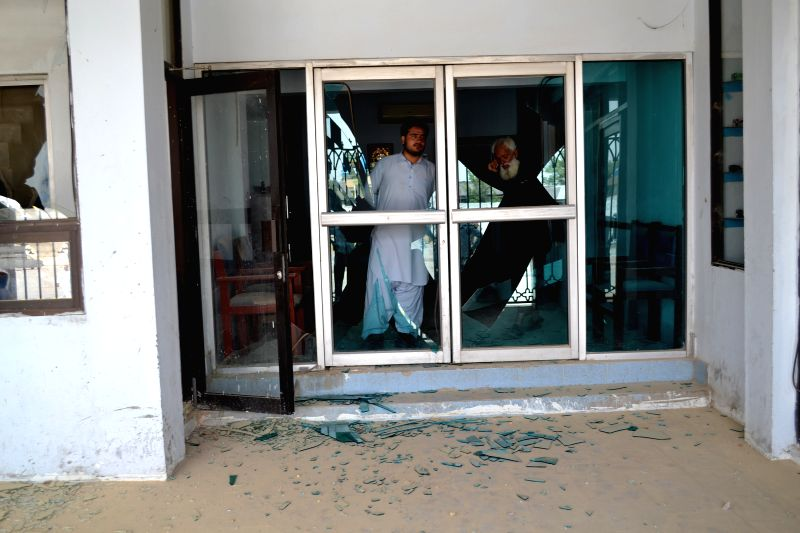 QUETTA, Aug. 11, 2016 - People inspect shattered glass doors near the blast site in southwest Pakistan's Quetta, Aug. 11, 2016. At least 12 people including four security personnel were injured in a ...