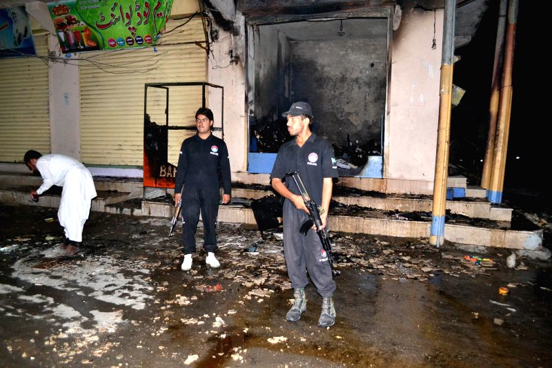 A policeman stands guard at the blast site in southwest Pakistan's Quetta on Aug. 12, 2014. At least nineteen people were injured in two separate blasts in Quetta on