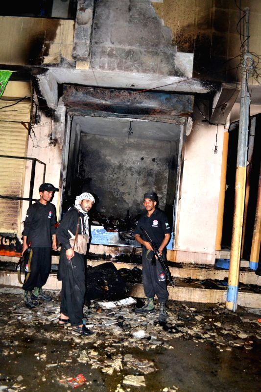 Policemen inspect the blast site in southwest Pakistan's Quetta on Aug. 12, 2014. At least nineteen people were injured in two separate blasts in Quetta on Tuesday ..