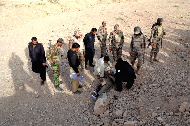 Pakistani security personnel examine the body of an attacker following an attack by militants in southwest Pakistan's Quetta, Aug. 15, 2014. Pakistan's Air Force ...