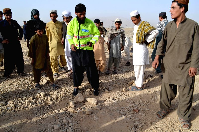 People examine the site near military airbases after an overnight attack by militants in southwest Pakistan's Quetta, Aug. 15, 2014. Pakistan's Air Force said Friday