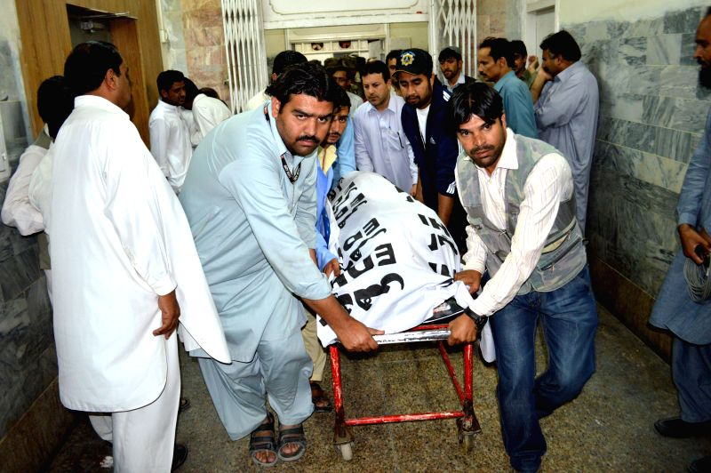 People transfer the body of a journalist to a hospital in southwest Pakistan's Quetta on Aug. 28, 2014. At least three people working for a local news agency were ...