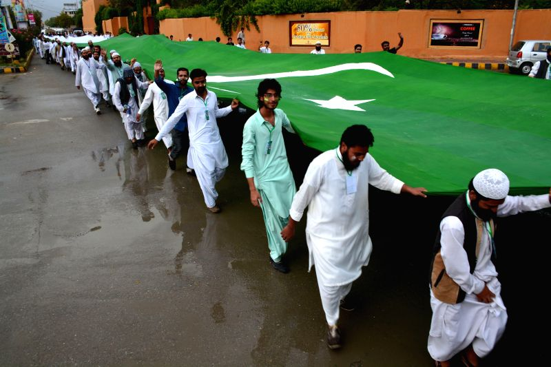 QUETTA, Aug. 6, 2016 - Pakistani people carry a giant Pakistani national flag during a rally ahead of the country's Independence Day in southwest Pakistan's Quetta, Aug. 6, 2016. Pakistan will ...