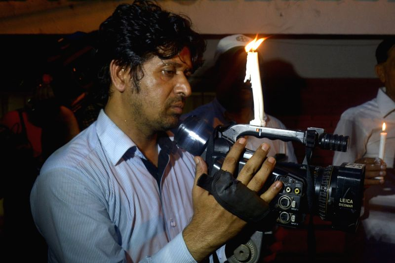 QUETTA, Aug. 8, 2016 - A journalist lights a candle on his gear during a vigil to condemn the deadly hospital bomb blast in Quetta, in eastern Pakistan's Lahore on Aug. 8, 2016. At least 70 people ...