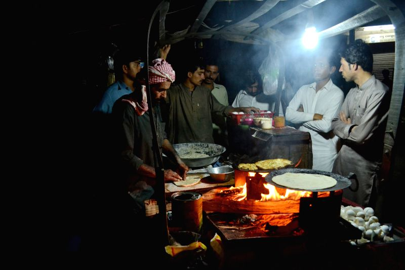 People buy traditional food during the holy fasting month of Ramadan in southwest Pakistan's Quetta, July 1, 2014.