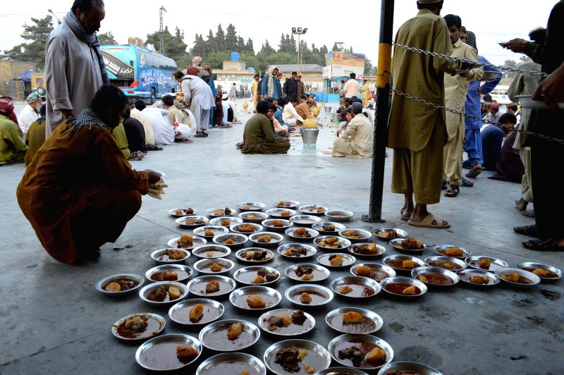 Men prepare Iftar food for Muslim devotees waiting to break their fast during the holy fasting month of Ramadan in southwest Pakistan's Quetta on July 5, 2014. ...