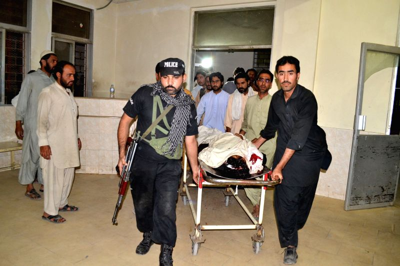 People transfer a body of a policeman to a hospital in southwest Pakistan's Quetta on July 6, 2014. At least two policemen were killed and two others were injured as .