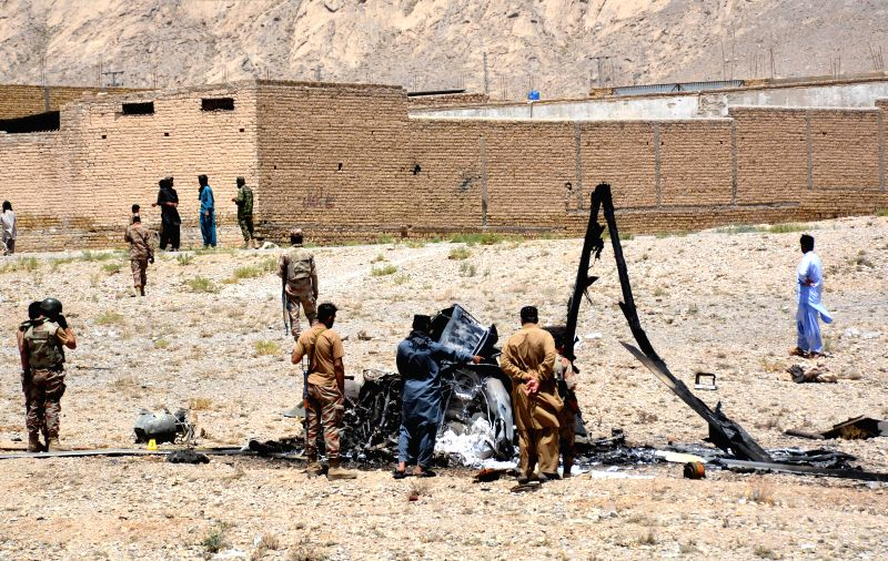 QUETTA, June 7, 2018 - Pakistani security officials gather around the wreckage of an army helicopter after a crash on the outskirts of Quetta, southwest Pakistan, on June 7, 2018. Two crew members ...