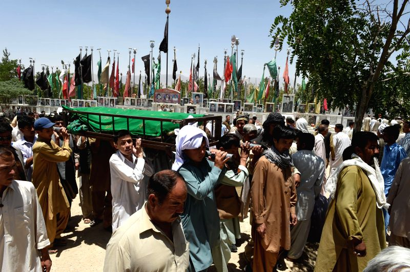 Pakistani Hazara Shiite Muslim community members attend a funeral ceremony for victims of the attack on shops in southwest Pakistan's Quetta on June 8, 2015. At least ...