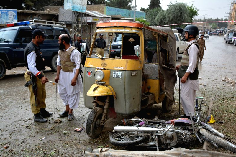 QUETTA, May 10, 2016 - Policemen inspect damaged vehicles at the explosion site in southwestern Pakistan's Quetta on May 10, 2016. At least 2 policemen were killed and 11 others injured when a blast ...
