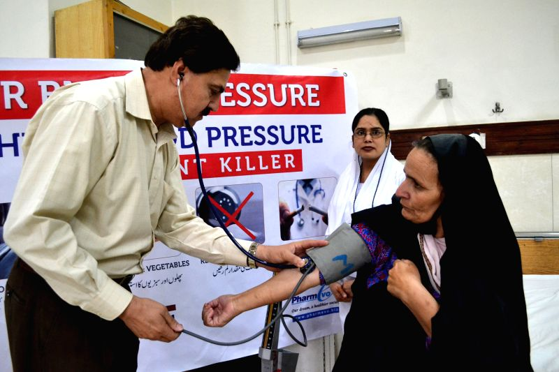A Pakistani doctor checks blood pressure of a patient during the World Hypertension Day in southwest Pakistan's Quetta, May 17, 2014. According to Global Burden of ...