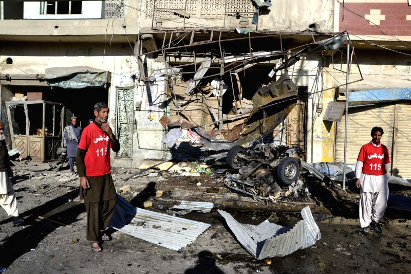 Quetta (Pakistan): Rescuers stand at a blast site in southwest Pakistan's Quetta, on Dec. 4, 2014. At least one man was killed and nine others wounded when a bomb exploded near a vegetable market ...