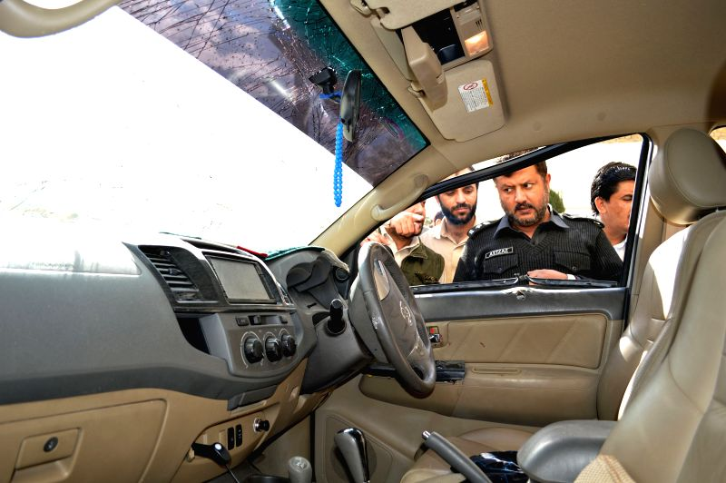 Policemen examine a damaged vehicle following a blast in southwest Pakistan's Quetta, Dec. 2, 2014. Two people were injured when a bomb exploded near the convoy of a senior official in ... - Balochistan