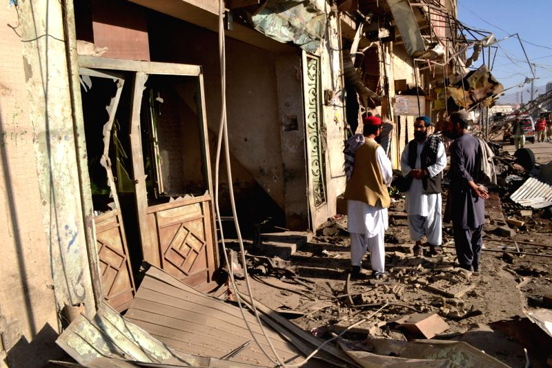 QuettaPeople stand beside damaged shops at the blast site in southwest Pakistan's Quetta, Dec. 4, 2014. At least one man was killed and nine others wounded when a bomb exploded near a vegetable ...