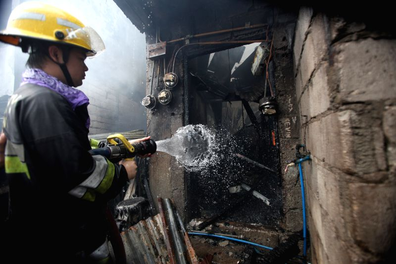 Quezon City: A firefighter puts out fire at a slum area in Quezon City, the Philippines, Nov. 18, 2014. It is believed that two people were killed and three others injured in the fire accident ...