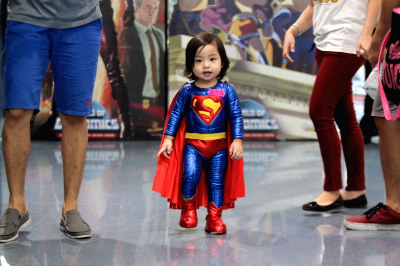 """A child dressed as the superhero """"Superman"""" walks to participate in the Super Hero World Record event in Quezon City, the Philippines, April 18, ..."""