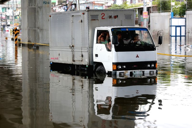 QUEZON CITY, Aug. 3, 2018 - A truck is immobilized by the flood after a heavy monsoon rain in Quezon City, Metro Manila, the Philippines, Aug. 3, 2018. Several streets and residential areas in Metro ...