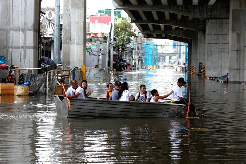 QUEZON CITY, Aug. 3, 2018 - Residents ride a boat along a flooded road after a heavy monsoon rain in Quezon City, Metro Manila, the Philippines, Aug. 3, 2018. Several streets and residential areas in ...