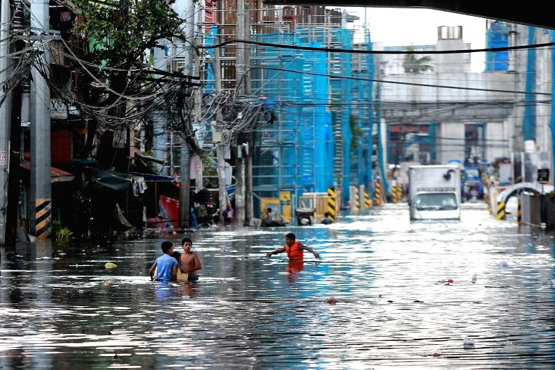 QUEZON CITY, Aug. 3, 2018 - Residents wade through a flooded road after a heavy monsoon rain in Quezon City, Metro Manila, the Philippines, Aug. 3, 2018. Several streets and residential areas in ...
