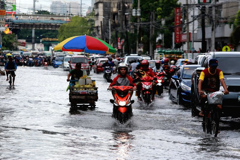QUEZON CITY, Aug. 3, 2018 - Vehicles move along a flooded road after a heavy monsoon rain in Quezon City, Metro Manila, the Philippines, Aug. 3, 2018. Several streets and residential areas in Metro ...
