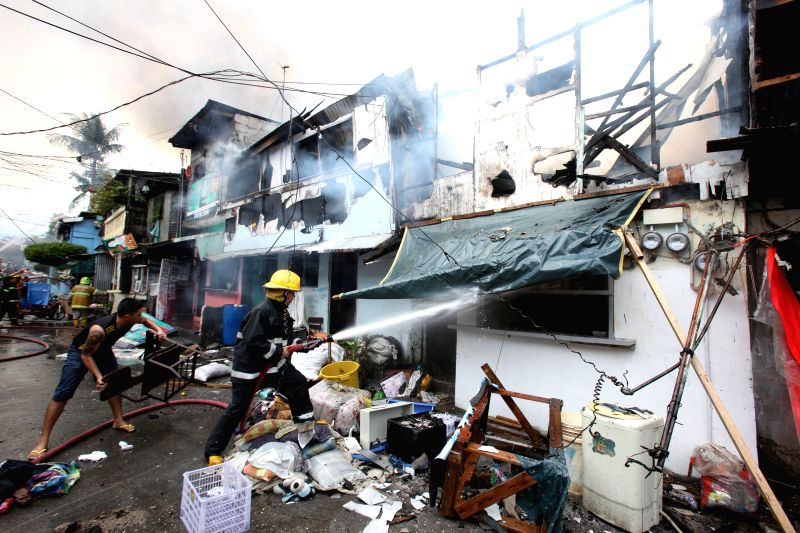 A firefighter and a resident try to put out a fire that hit a slum area in Quezon City, the Philippines, Dec. 17, 2014. More than 150 families lost their homes .