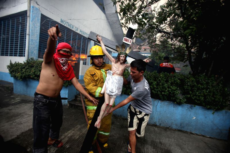 A firefighter evacuates a crucifix from a burning chapel during a fire that broke out at a residential area in Quezon City, the Philippines, on Jan. 1, 2015. The