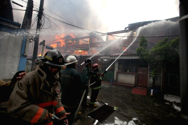 Firefighters try to put out a fire that broke out at a residential area in Quezon City, the Philippines, on Jan. 1, 2015. The fire razed more than 200 houses, ...