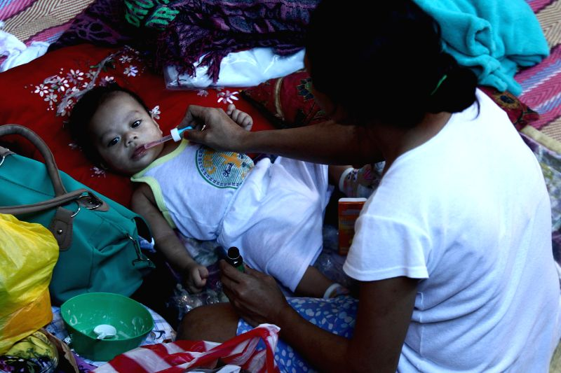 A mother gives vitamins to her son inside a basketball court turned into an evacuation center after a fire in Quezon City, the Philippines, Jan. 2, 2015. The ...
