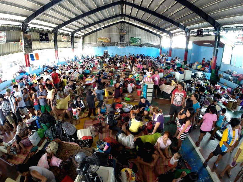 People take shelter inside a makeshift evacuation center at a basketball court after a fire in Quezon City, the Philippines, Jan. 2, 2015. The fire razed more ...