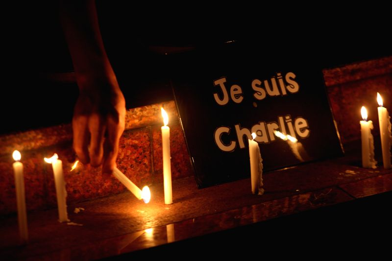 "A member of the National Union of Journalists of the Philippines (NUJP) lights candles in front of a placard that reads ""je suis Charlie"" (I am ..."