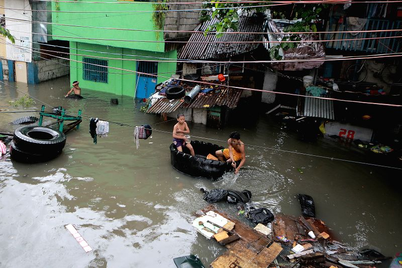 QUEZON CITY, July 17, 2018 - Residents use a discarded tyre as they wade through flood water brought by the heavy rain in Quezon City, the Philippines, July 17, 2018.